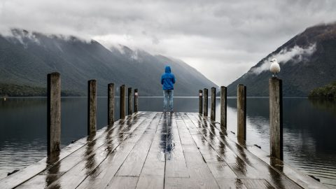 man in blue on a bridge mountains